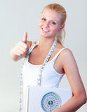 Attractive woman with thumb up holding a scales Stock Photography