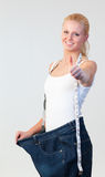 Attractive woman with thumb up wearing big jeans Royalty Free Stock Image