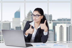 Attractive woman with thumbs up in office Royalty Free Stock Photo