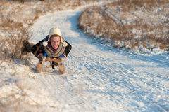 Attractive woman tobogganing downhill Royalty Free Stock Photography