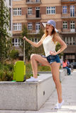 Attractive woman tourist with suitcase ready to travel. Adventure, teenage journey concept. Attracitve woman ready to travel wearing denim shorts, white top and Stock Images