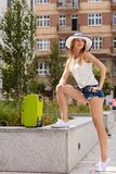 Attractive woman tourist with suitcase ready to travel. Adventure, teenage journey concept. Attracitve woman ready to travel wearing denim shorts, white top and Royalty Free Stock Photography