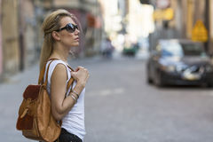 Attractive  woman tourist in sun-glasses with a small backpack visiting the old town. Royalty Free Stock Photo