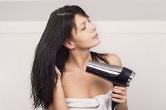 Attractive woman in a towel blow drying her hair Stock Image