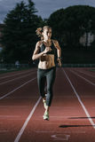 Attractive woman Track Athlete Running On Track. Royalty Free Stock Photography