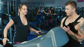 Attractive woman training on a treadmill. With personal trainer stock video
