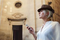Attractive woman traveler in trendy hat waiting for the call on her cell telephone during recreation time Stock Photos