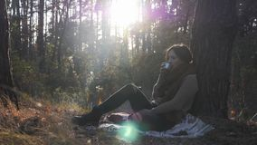 Attractive woman traveller drinking hot tea on nature. Young beautiful female brunette drinking coffee in autumn forest at sunny w. Arm day stock footage