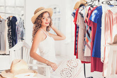 Attractive woman trying on a hat. Happy summer shopping. Attractive woman trying on a hat. Happy summer shopping concept stock image