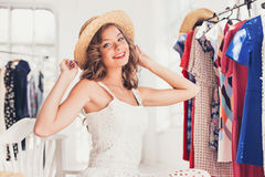 Attractive woman trying on a hat. Happy summer shopping. Attractive woman trying on a hat. Happy summer shopping concept stock photos