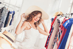 Attractive woman trying on a hat. Happy summer shopping. Attractive woman trying on a hat. Happy summer shopping concept stock photo