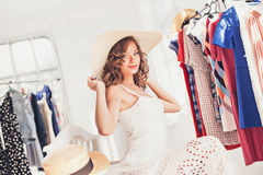 Attractive woman trying on a hat. Happy summer shopping. Attractive woman trying on a hat. Happy summer shopping concept stock images