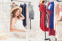 Attractive woman trying on a hat. Happy summer shopping. Attractive woman trying on a hat. Happy summer shopping concept stock photography