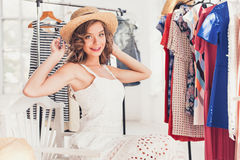 Attractive woman trying on a hat. Happy summer shopping. Attractive woman trying on a hat. Happy summer shopping concept royalty free stock image