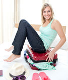 Attractive woman trying to close her suitcase Stock Photography