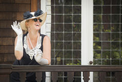 Attractive Woman in Twenties Outfit on Porch of Antique House Royalty Free Stock Photos