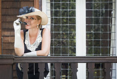 Attractive Woman in Twenties Outfit on Porch of Antique House Royalty Free Stock Photo