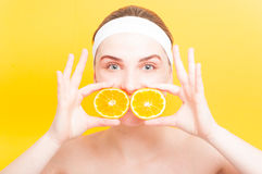 Attractive woman with two slices of orange fruit Royalty Free Stock Images