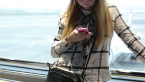 Attractive woman are typing on the mobile phone, waiting for a plane. Young beautiful woman typing message on a mobile stock video footage