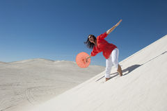 Attractive woman with umbrella on desert sand dune Royalty Free Stock Images