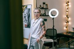 Attractive woman with unusual appearance working as tattoo master royalty free stock image