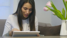 An attractive woman uses her new digital tablet in her living room stock footage