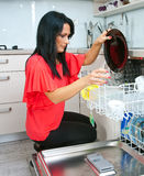 Attractive woman using dishwasher Royalty Free Stock Images