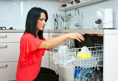 Attractive woman using dishwasher Stock Photography