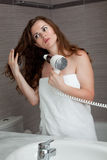 Attractive woman using fen in bathroom stock images