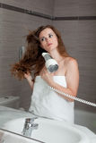 Attractive woman using fen in bathroom Royalty Free Stock Image