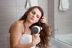 Attractive woman using fen in bathroom. Dressed in towel beautiful woman using fen at modern bathroom royalty free stock photo