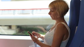 Attractive woman using her phone on her train journey stock footage