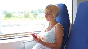 Attractive woman using her phone on her train journey stock video footage
