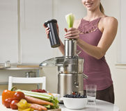 Attractive woman using juicer Stock Photo