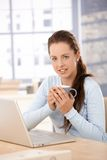 Attractive woman using laptop at home drinking tea Royalty Free Stock Photo