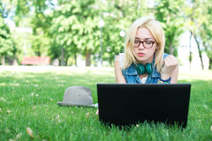 Attractive woman using laptop in the park lying Royalty Free Stock Images