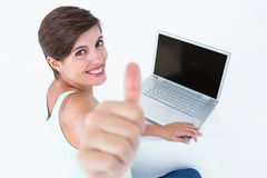 Attractive woman using laptop with thumb up Stock Image