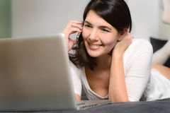 Attractive woman using a mobile phone and a laptop Royalty Free Stock Photo