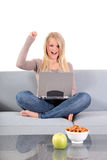 Attractive woman using notebook computer. An attractive young woman using her notebook computer while sitting on a comfy couch Stock Photos