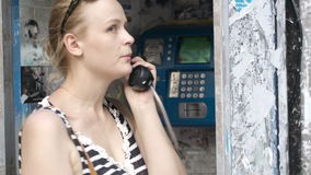 Attractive woman using a public telephone stock video