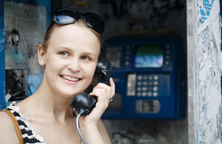 Attractive woman using a public telephone Royalty Free Stock Photography