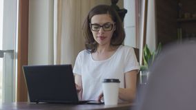 Attractive woman using smartphone and laptop at home. Young beautiful female in eyeglasses sitting at home before laptop and using smartphone stock video