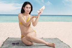 Attractive woman using suntan lotion Royalty Free Stock Photo