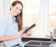 Attractive woman using tablet device Royalty Free Stock Images