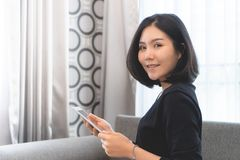 Attractive woman using tablet on sofa stock photo
