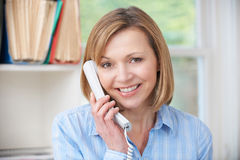 Attractive Woman Using Telephone In Home Office Stock Images