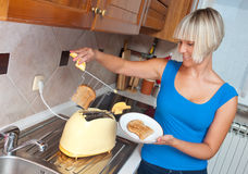 Attractive woman using toaster Stock Image