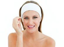 Attractive woman using tweezers Royalty Free Stock Photos