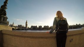 Attractive woman vising London city looking Big Ben and the House of parliament standing near Thames river -. Attractive woman vising London city looking Big Ben stock video footage
