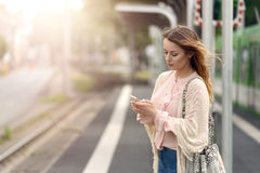 Attractive woman waiting on a platform. Attractive stylish young woman waiting alone on a platform at a small urban station checking her mobile phone for Royalty Free Stock Images
